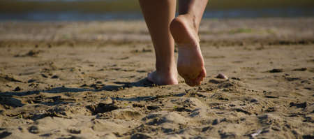 woman stepping barefoot on the beach sand Stock Photo