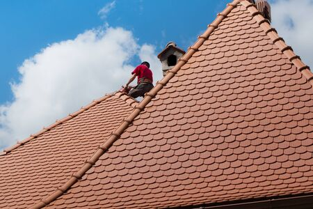 roofing worker on the house during daylight Stock Photo