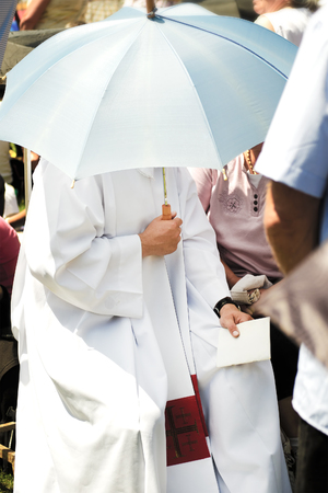catholic priest dressed with white clothes in daylight