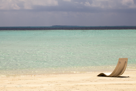 idling: Beach chair on the white sand beach with cloudy blue sky and sun Stock Photo