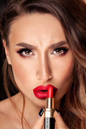 applying lipstick: Professional Lips Make-up. Red lips. Lipstick. Beauty Girl Applying Lipstick