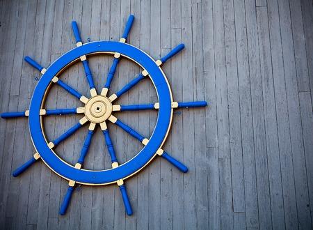 piloting: Blue Ship Wheel on wooden background, marine style