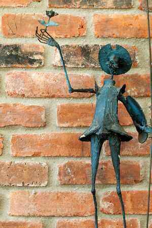 don quijote: Don Quijote de entregar una estatua rosa en el fondo de pared de ladrillo