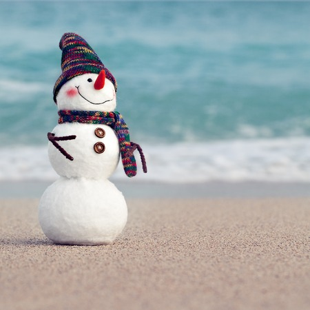 sunshade: Smiling snowman on the sea beach. Summer holidays or New Year concept