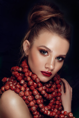 cheekbones: Beauty Fashion Model Girl with Perfect Make up, Long Lushes. Big Beads Necklace. Nail Art. Red Lipstick and Nail Polish. Isolated on black background Stock Photo