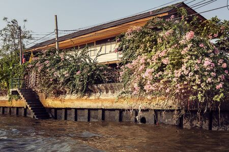 Wooden slums on stilts on the riverside of Chao Praya River in Bangkok, Thailand Stock Photo