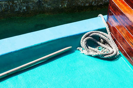 fastened: White mooring rope on boat or ship, shallow dof, tinted blue, copy space