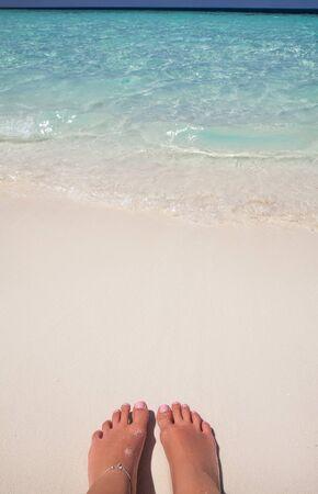 sandy feet: Vacation holidays. Woman feet closeup of girl relaxing on beach on sunbed enjoying sun on sunny summer day. sandy feet on the beach