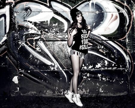 fashion art: Pretty young woman near graffiti wall, black and white Stock Photo