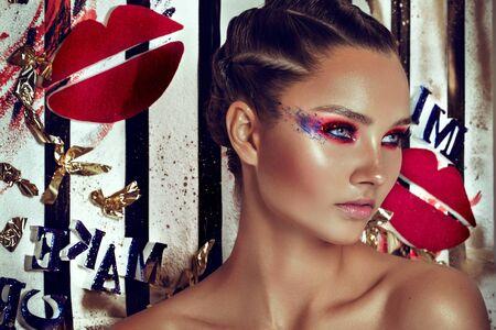 Moda Modelo de la muchacha. Mujer de fiesta durante Brillante fondo brillante. Moda Chica del arte del retrato con el pelo violeta. Peinado y maquillaje creativo. Maquillaje. Fiesta nocturna. Componen concepto