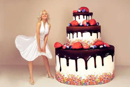 魅力的な女性が大きなケーキの近くのマリリン ・ モンローのようなポーズします。ピンク色の背景上に分離。お祝いのコンセプトです。