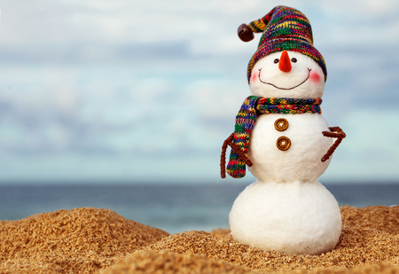 christmas snowman in red santa hat and sunglasses at sunny beach. Holiday concept for New Years Cards Stock Photo