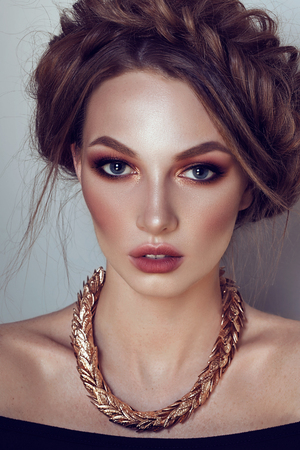 Beautiful girl with the Golden makeup and golden jewelry. Fashion woman Portrait.