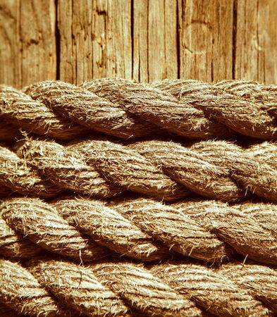 marine rope on weathered old wood background.