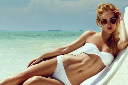 Summer girl model with tanned sexy body. Posing in the white chair on the beach of the tropical island. Standard-Bild
