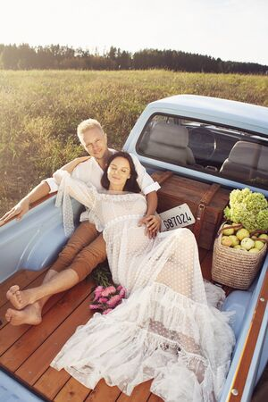 Pregnant woman and her husband happy together and looking each other with love. Outdoor photoshoot in the car