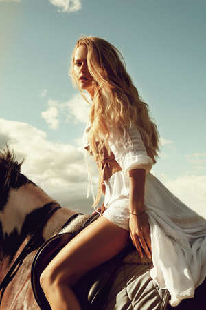 beautiful blonde woman riding a horse in summer day. Romantic fashion style