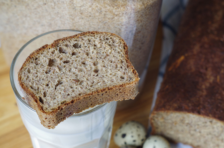 Slice of homemade gluten free bread on glass of milk, with linseed flour and psyllium husk.
