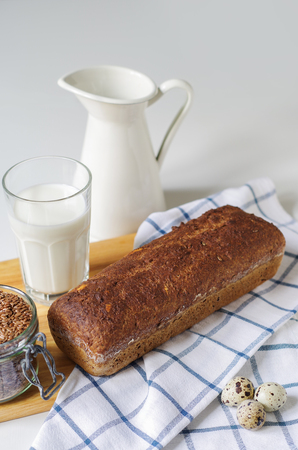 Homemade gluten free bread with linseed flour and psyllium husk. Jug and glass of milk, linen seed in glass jar. Quail eggs on kitchen towel Stock Photo
