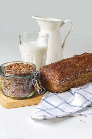 Homemade gluten free bread with linseed flour and psyllium husk. Jug and glass of milk, linen seed in glass jar Stock Photo