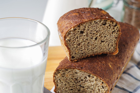 Homemade gluten free bread with linseed flour and psyllium husk. Glass of milk