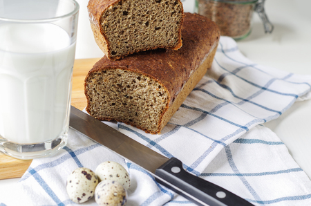 Homemade gluten free bread with linseed flour and psyllium husk. Glass of milk,quail eggs on a kitchen towel