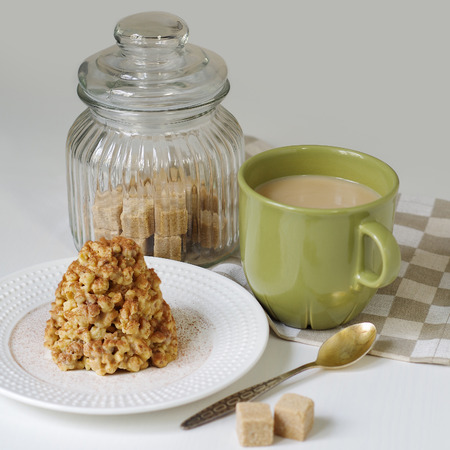 condensed: Cake anthill on a white plate with cup of coffee.  Coffee in a green mug and dessert from a shortbread in the form of a hill