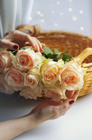 Womens hands hold a woven basket with bunch of pale pink cream roses. Soft focus. Romance background with copy space.