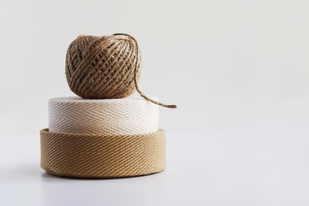 Rolls of beige canvas strapping tape and rope
