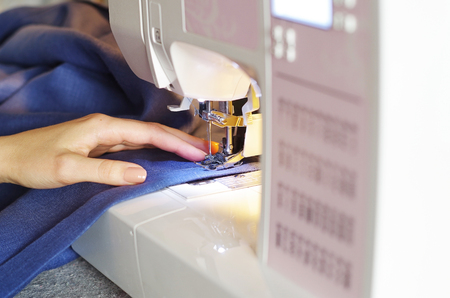 Womens hands of seamstress using sewing machine. Tailoring Process