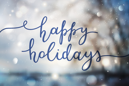 happy holidays, lettering on winter blurred background