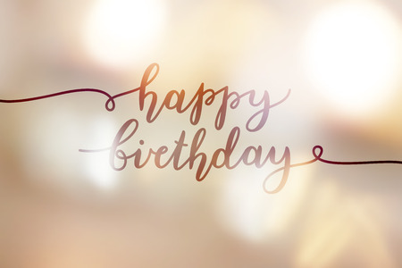 happy birthday, lettering on golden blurred background of lights