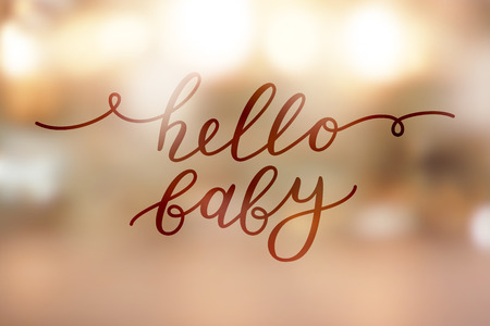 Hello baby lettering on golden blurred lights.
