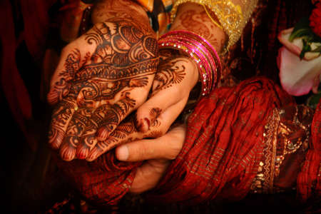 A groom holds the beautifully decorated hands of his new bride