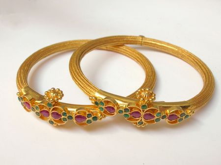 A close up of Two  Gold Bangles on white  photo