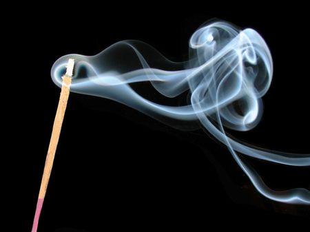 smoke of incense sticks burning over black