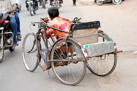 Hyderabad,AP,India-August 9,2011- Handicapped man trying to cross the busy road on his tricycle. Stock Photo - 11016956