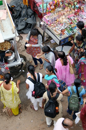 india food: Hyderabad,AP,India-August 9,2011-Group of indian girl students eating street food in a busy market.