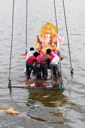 pooja: Hyderabad,AP,India-September 4,2011-Hindus immesing the Ganesh Idol  in lake during vinayaka chathurthi.