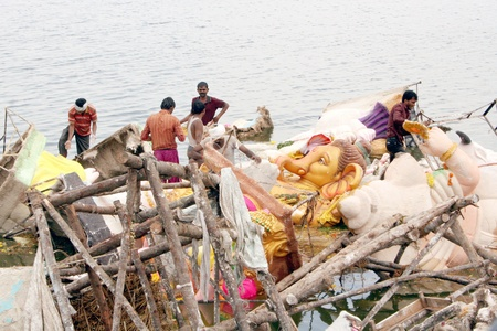 plaster of paris: Hyderabad,AP,India-September 12,2011-Workers removing the ganesh idols immersed in the tank ,on the ganesha nimajjanam festivals