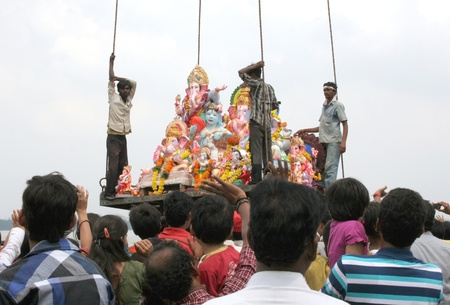 immersion: Hyderbad,Ap,India- September 29,2012-People use crane to lift Lord Ganesha idol for the traditional immersion during Hindu festival ganesh chathurthi,an annual event.  Editorial