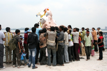 immersion:  Hyderbad,Ap,India- September 29,2012-People push Lord Ganesha idol in to water from the tank bund for immersion during Hindu festival ganesh chathurthi,an annual event.