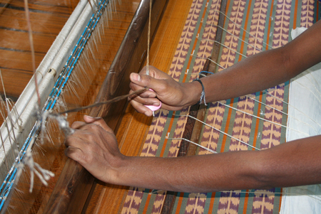 rug weaving: Woman working at the loom-hand loom weaving saree Stock Photo
