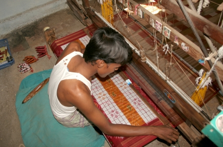weaving: Hyderabad,AP,India-April 15,2012-Weaver working on handloom