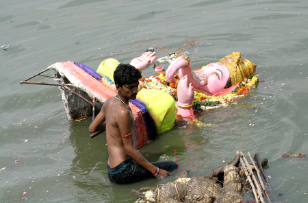 Hyderabad,Ap,India- September 15,2013 Man remove ganesha idol, after immersion,during hindu festival  Every year pollutants are removed immediately after immersion  Editorial