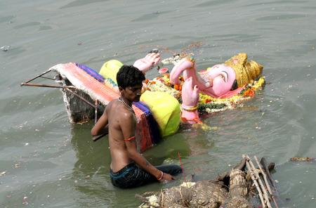 contaminacion ambiental: Hyderabad, AP, India, septiembre 15,2013 hombre remove ganesha ídolo, después de la inmersión, durante el festival hindú Cada año, los contaminantes se eliminan inmediatamente después de la inmersión