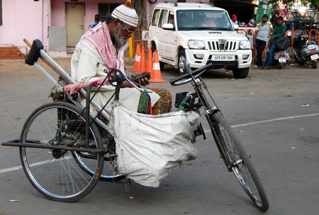 people with disabilities: Hyderabad,India-March 17,2015:Indian senior handicapped man on a tricycle begging on a busy road. Editorial