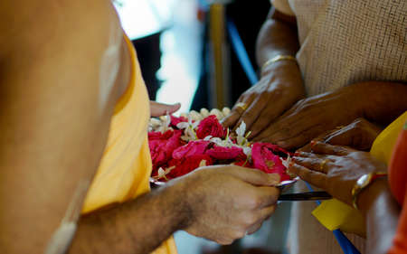 View of Indian Hindu people touch the flowers which are to be used in offering prayers to god by the priest Reklamní fotografie