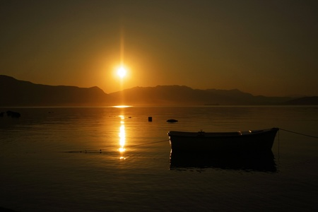 Sunrise boat in the see with mountains photo