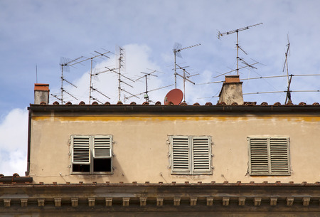 Satellite dish and antennas TV on an old mediterranean house photo
